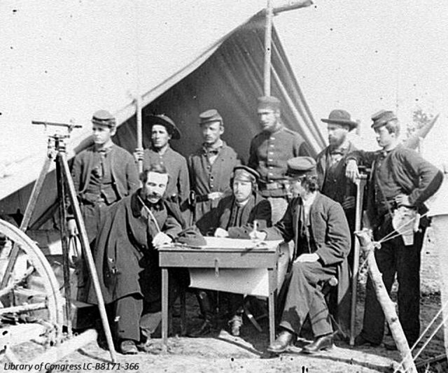 This photograph was taken in 1862 at Yorktown, VA.  It shows a typical survey crew of the period. There is a mix of military and civilian members. They also proudly display some of their equipment; the theodolite on the left, the prismatic compass attached to the man's belt on the right, and a survey table in the center.